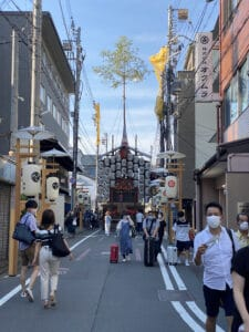 People wearing masks walk near a Gion Festival float while wearing masks.